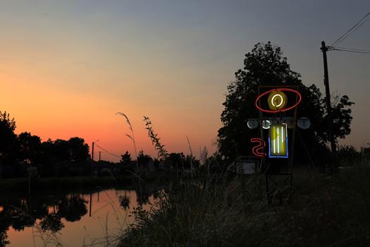 """BLACK SUN (Motel), assemblage d'anciennes enseignes, néons, acier, câbles et variateurs électriques. Activation nocturne de l'oeuvre  lumineuse exposée lors """"d'Horizons d'eaux 4"""", parcours d'art contemporain  sur le canal du Midi réalisé en partenariat par les Abattoirs, Musée – Frac Occitanie Toulouse, le Festival Convivencia et le Frac Occitanie Montpellier. Ce travail a reçu le soutien de la Région Occitanie."""